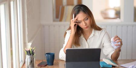 Belle femme d'affaires asiatique fatiguée travaillant avec des maux de tête dans une salle de bureau moderne