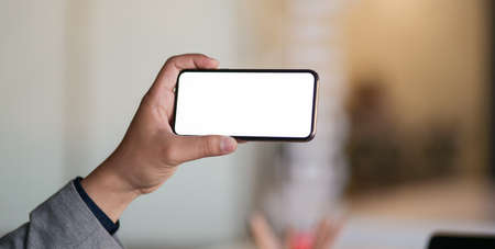 Cropped shot of professional businessman showing blank screen smartphone in office room