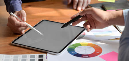 Cropped shot of young professional graphic designer working on blank screen tablet in workplace
