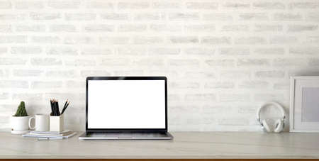 Cropped shot of modern stylish workplace with open blank screen laptop computer and office supplies on marble desk and brick wall background Banco de Imagens