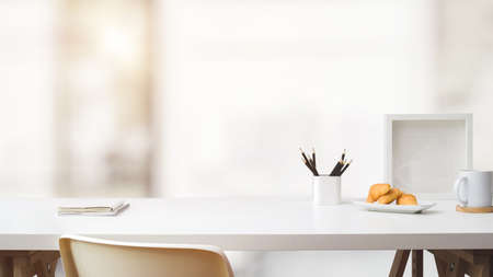 Close up view of simple workspace with copy space, frame, stationery, coffee cup and croissant on white table with blurred background