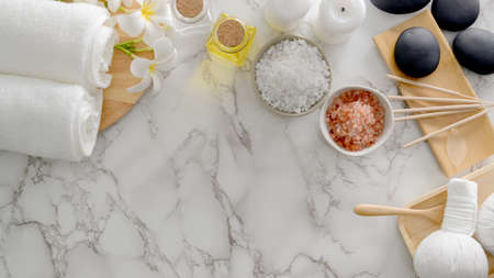 Top view of Beauty spa treatment and relax concept with aroma stick, spa salt, hot stone and other spa accessories on marble desk  background Stock Photo