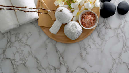 Overhead shot of Beauty spa treatment and relax concept with white towel, spa salt, hot stone and other spa accessories on marble table  background Stock Photo