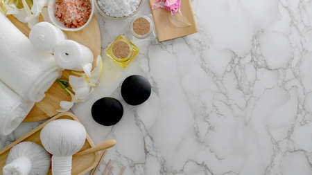 Overhead shot of Beauty spa treatment and relax concept with white towel, spa salt, hot stone and other spa accessories on marble desk  background