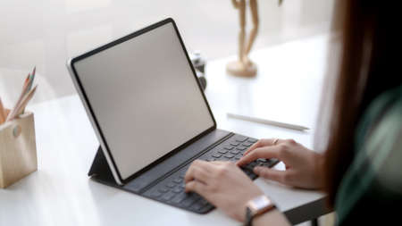 Close up view of female designer typing on blank screen tablet with wooden figure and coloured pencils on white table in simple co working space