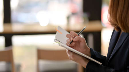 Side view of female freelancer writing on mock up notebook with pencil while sitting in simple co working space Stock Photo