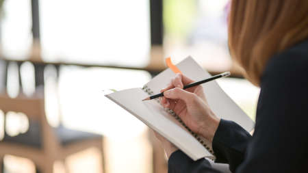 Cropped shot of female freelancer writing on mock up notebook with pencil while sitting in simple co working space