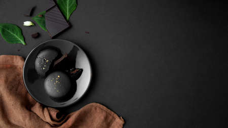 Top view of dark chocolate macarons on black plate with copy space, leaves and brown napkin decorated on dark table background