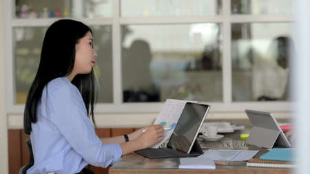 Side view of businesswoman focusing on her work with digital tablet and document file on wooden table in simple co-working space