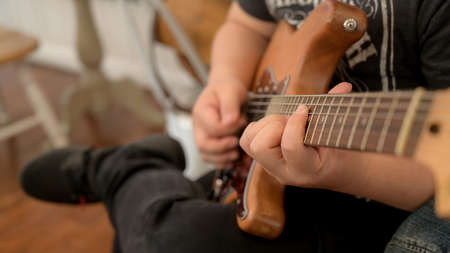 Cropped shot of male musician practicing guitar while siting on chair in music instrument
