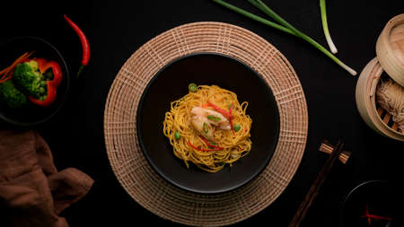 Top view of Schezwan Noodles or Chow Mein with vegetable, chicken and chilli sauce served in black bowl and ingredients on black table