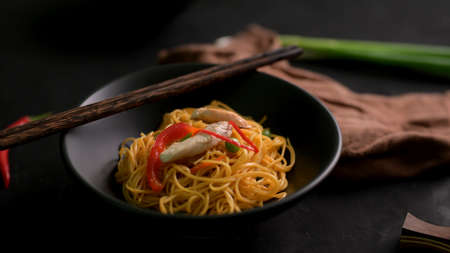 Cropped shot of Schezwan Noodles or Chow Mein in black bowl with chopsticks on black table