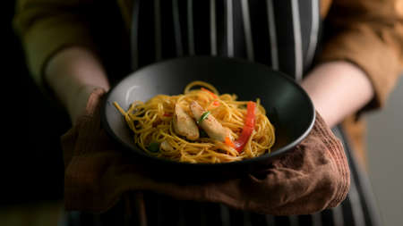 Close up view of a woman holding Schezwan Noodles or Chow Mein bowl