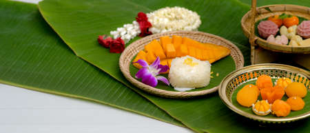 Close up view of several Thai traditional dessert serving on brass tray and wooden tray with jasmine garland and banana leaves decorated on white table