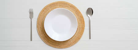 Top view of white plank dinning table with white ceramic plate on placemat and silverware