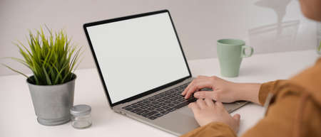 Cropped shot of female employee typing on blank screen laptop on white simple worktable with mug and decorations 版權商用圖片