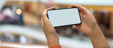 Close up view of a girl holding horizontal mock-up smartphone while standing at balcony in shopping mall