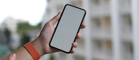 Close up view of hand holding blank screen smartphone while standing at balcony