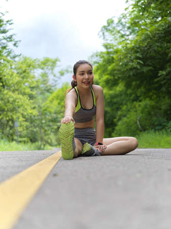 Portrait of female in sportswear stretching her leg to cool down after morning exercises in nature