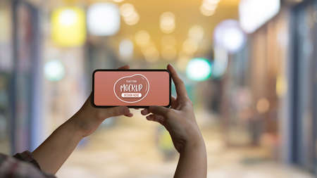 Close up view of female hands holding mock up horizontal smartphone screen in  blurred mall background
