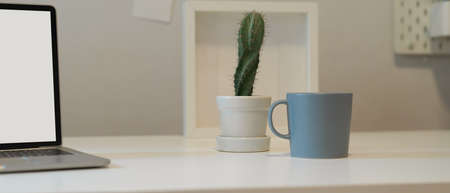 Close up view of home office desk with cactus pot, mug, frame and mock up laptop on white desk