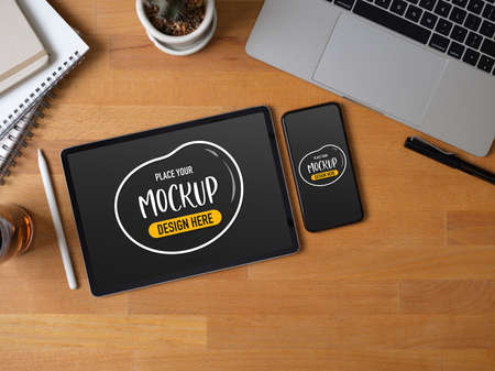 Top view of workspace with mock up tablet, smartphone, laptop, stationery and decoration on wooden table Archivio Fotografico