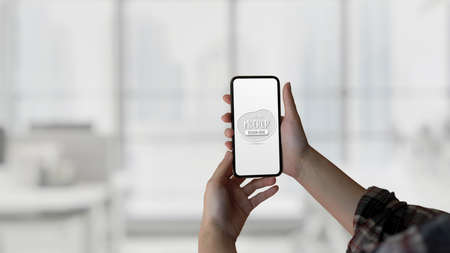 Close up view of female hands holding mock up smartphone in blurred background