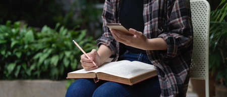 Close up view of female student reading book and using smartphone while sitting in garden