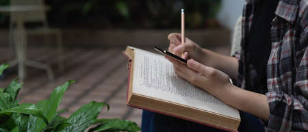 Side view of female student using smartphone to searching information while reading book in garden