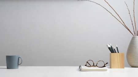 Close up view of study table with stationery, eyeglasses, notebook, mug, decoration and copy space in home office