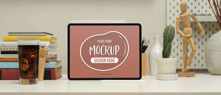 Close up view of worktable with mock up laptop , books, stationery, decorations and beverage in home office room Archivio Fotografico