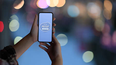Close up view of female hands holding mock up smartphone in bokeh background Archivio Fotografico
