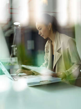 View through glass window of female office worker concentrating on her task with laptop and paperwork