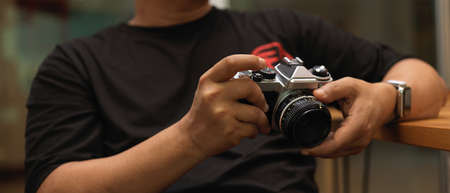 Close up view of male photographer holding digital camera while sitting at worktable in studio