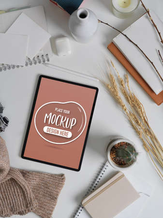 Top view of autumn workspace with mock up tablet, stationery, accessories and decorations on white table