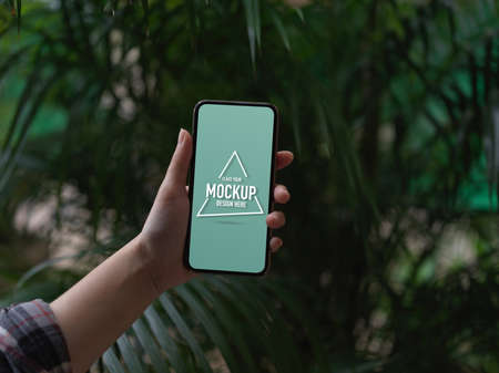 Close up view of female hand holding mock up smartphone while relaxing in garden Archivio Fotografico