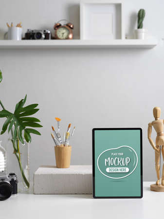 Cropped shot of modern home office with mock up digital tablet, camera, supplies, decorations and copy space on table Archivio Fotografico