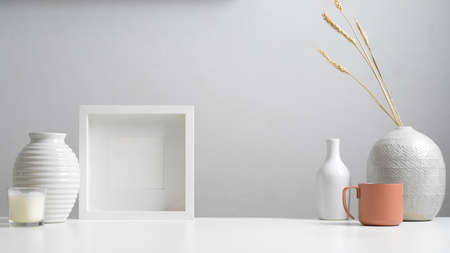 Close up view of minimal home interior design with copy space, mock up frame, vases and decorations in white concept