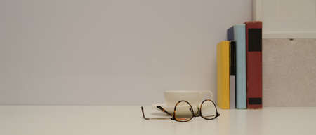 Close up view of study table with eyeglasses, books, cup, decorations and copy space on white table