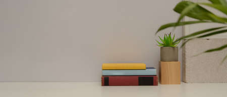Close up view of simple study table with copy space, books, plant vase and decorations on white table