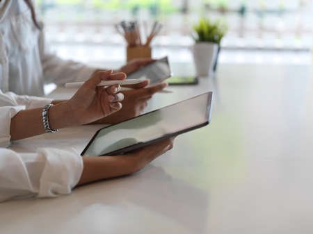 Side view of female hands using digital tablets while sitting beside each other in library