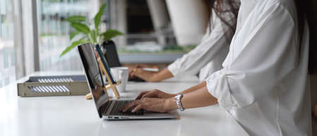 Side view of two female office workers working with laptop on office desk with office paper filing trays in office room Archivio Fotografico