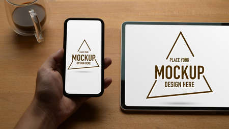 Close up view of male hand holding mock up smartphone on wooden table with mock up digital tablet and coffee mug