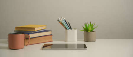 Close up view of study table with digital tablet, books, stationery, mug and decoration in living room