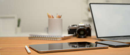 Close up view of workspace with digital tablet, laptop, camera, smartphone and stationery on wooden desk