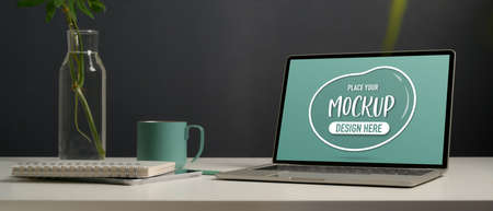 Close up view of mock up laptop, stationery, plant vase and mug on white desk in home office