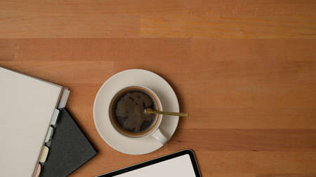 Top view of worktable with a cup of coffee, notebooks, mock up tablet and copy space on wooden table