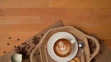 Top view of breakfast table with latte coffee cup and biscuits on tray decorated with coffee beans and placemat