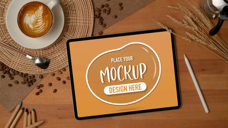 Top view of mock up digital tablet on breakfast table with a cup of latte coffee decorated with coffee beans and wheat