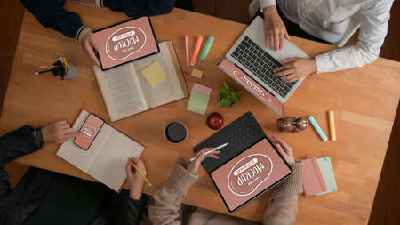 Top view of college students doing group assignment with mock up digital devices, books and stationery on wooden table